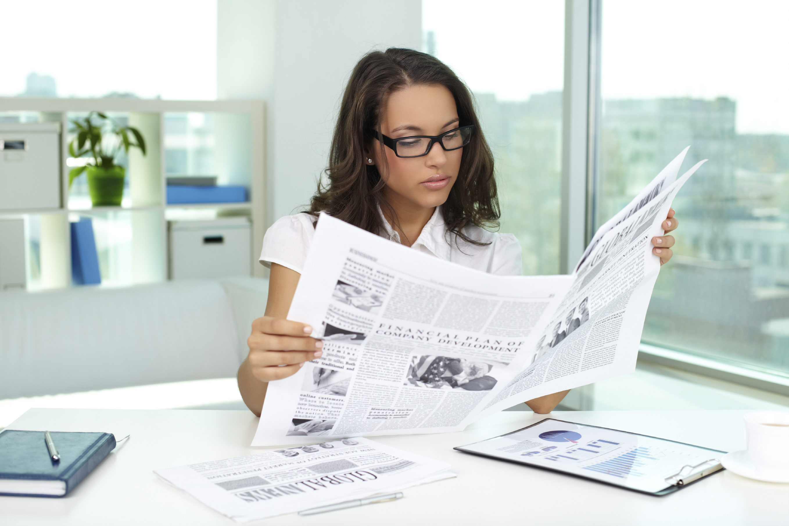 woman wearing glasses reading newspaper at her desk