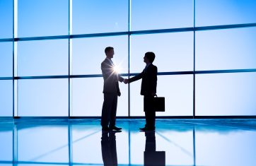 Two people shaking hands in front of a big open window