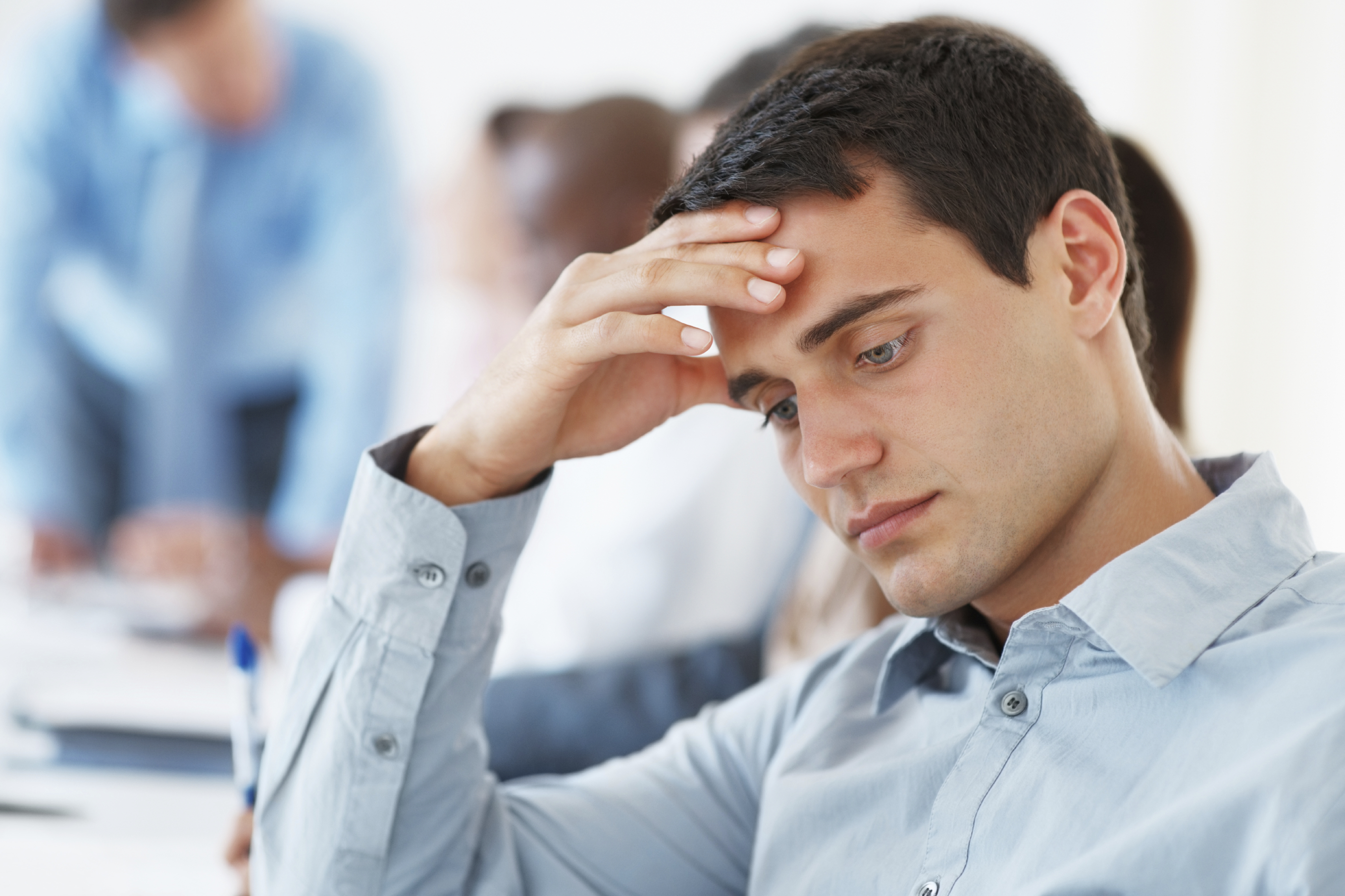 Closeup of bored business man sitting with hand on forehead with colleagues during meeting