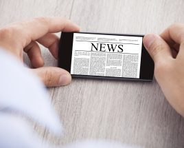 Cropped image of businessman surfing news on smartphone at desk