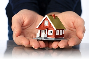 hands holding small house mortgage