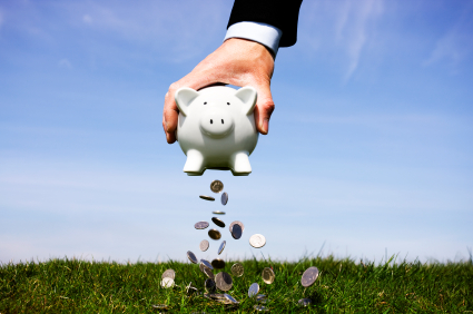 Person holding piggy bank and emptying the content onto the grass