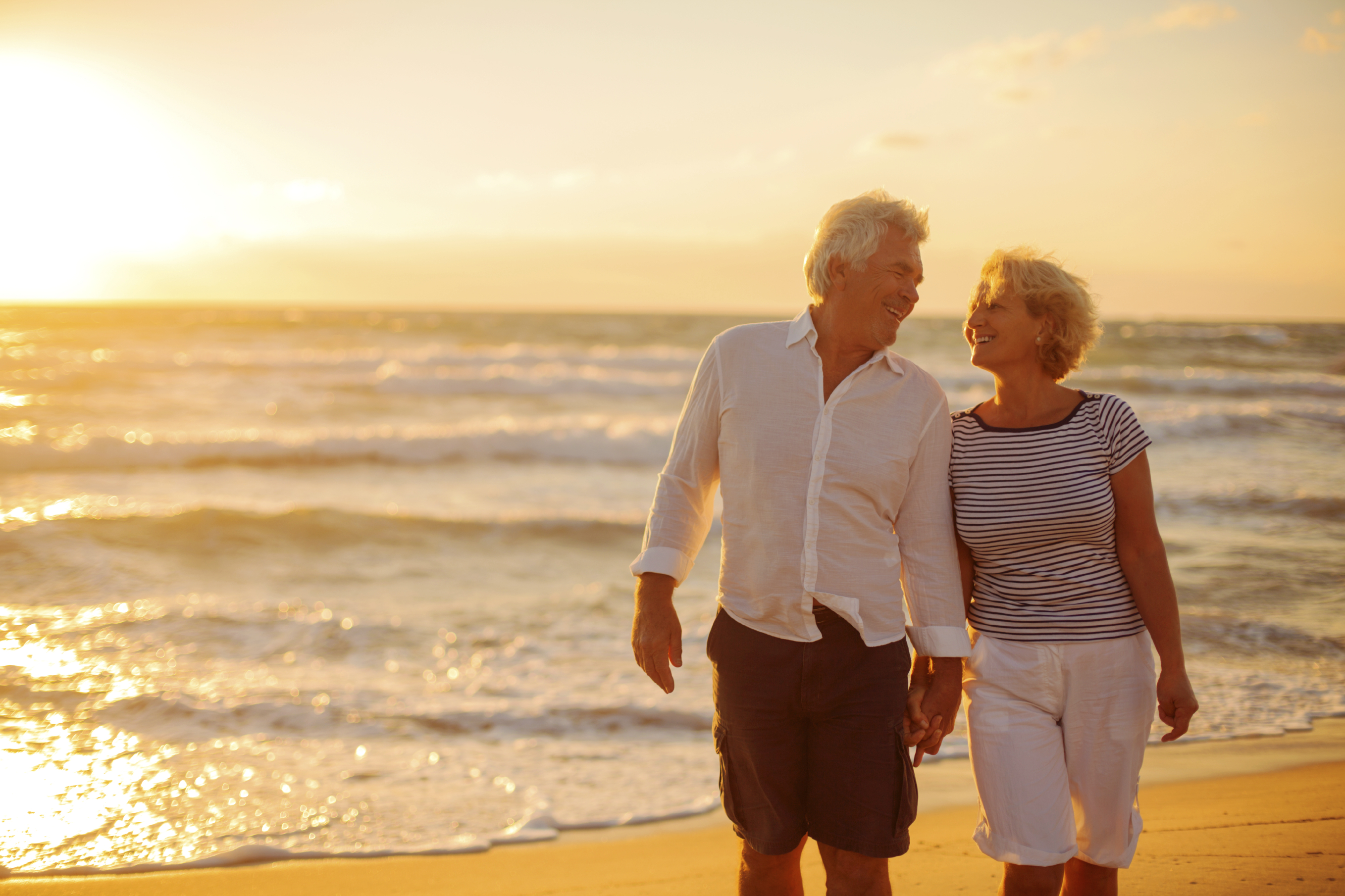 retired couple on the beach smiling at eachother with the sun shining