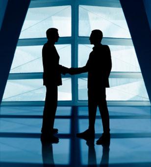 Two men shaking hands in front of big open window